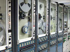 The machines pictured read the inch-wide magnetic data tape from their 14-inch reels. Multiple machines are used because each reel only records about 15 minutes worth of data. As one reel fills, the next machine automatically starts recording a slight overlap for data continuity.